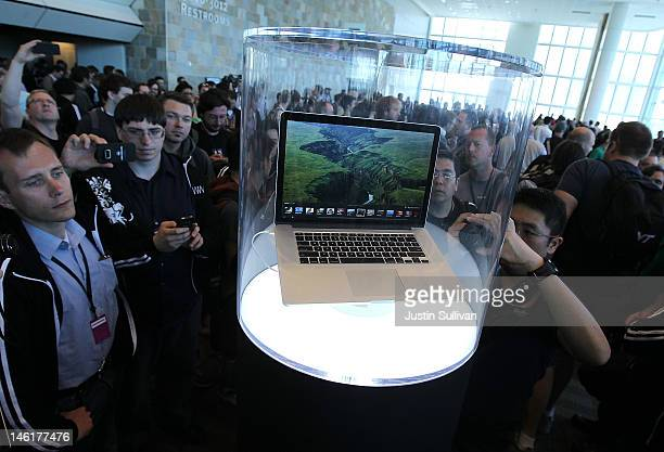 WWDC attendees look at the new MacBook Pro that is displayed at the 2012 Apple WWDC keynote address at the Moscone Center on June 11 2012 in San...