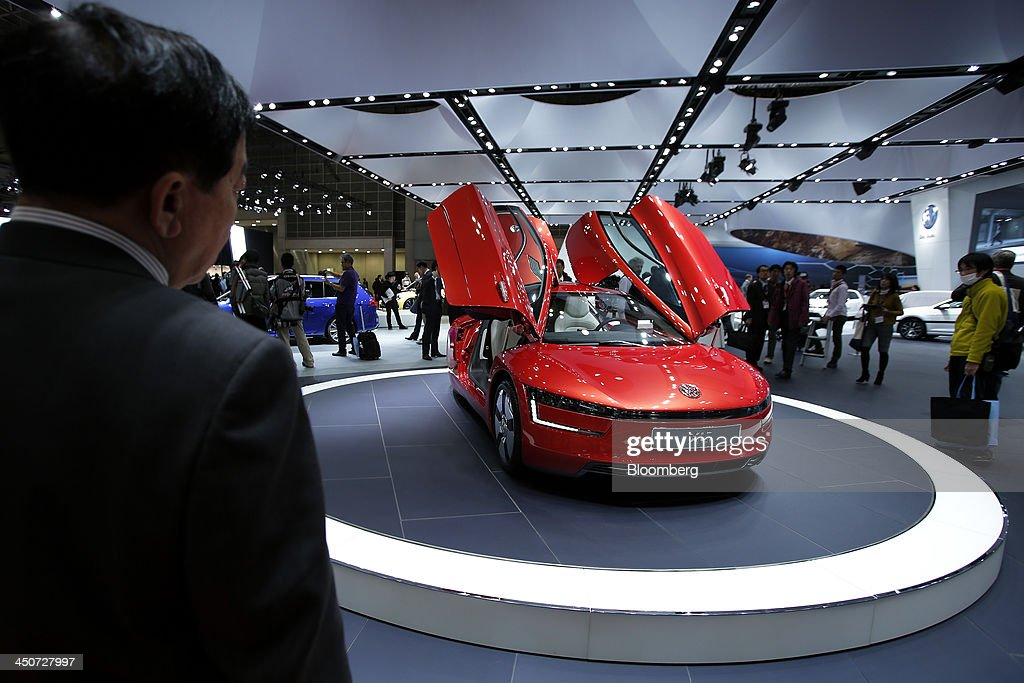 Attendees look at Volkswagen AG's (VW) XL1 vehicle on display at the 43rd Tokyo Motor Show 2013 in Tokyo, Japan, on Wednesday, Nov. 20, 2013. The autoshow will be open to the public from Nov. 23 to Dec. 1 at the Tokyo International Exhibition Center, also known as the Tokyo Big Sight. Photographer: Kiyoshi Ota/Bloomberg via Getty Images