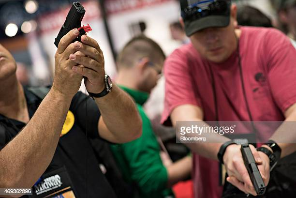 Attendees look over Glock Inc pistols on the exhibition floor of the 144th National Rifle Association Annual Meetings and Exhibits at the Music City...