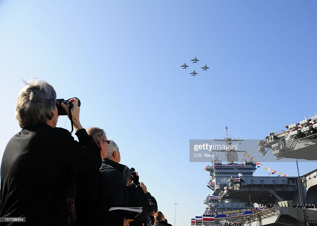 Attendees observe a ceremonial flyover during the inactivation ceremony for the aircraft carrier USS Enterprise (CVN 65)on December 1, 2012 in Norfolk Virginia.. Enterprise was commissioned in 1961 and is scheduled to celebrate her inactivation after 51 years of service.