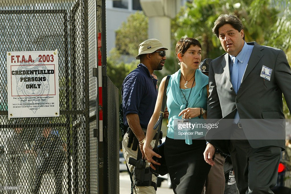 Attendees of a trade conference walk past barricades on the second day of the summit to create a Free Trade Area of the Americas (FTAA) November 18, 2003 in downtown Miami, Florida. Due to expected protests from anarchists, labor groups and globalization foes, much of the city of Miami is in a police lockdown, with thousands of businesses closed and a steel barricade circling the summit area.