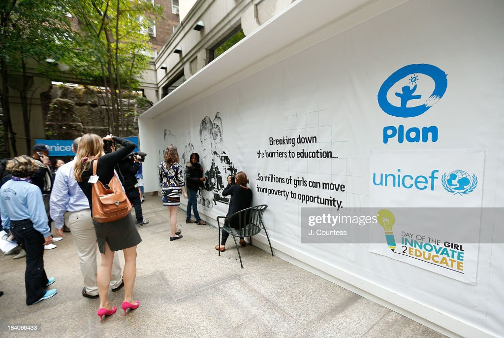 Attendees of the Innovate 2 Educate program, which marks International Day of the Girl, work on a giant erasable fresco staged by Plan International and UNICEF at UNICEF House on October 11, 2013 in New York City. The billboard portrays an image of girls working in a typical sweatshop, which when erased revealed girls in their rightful place, in the classroom.