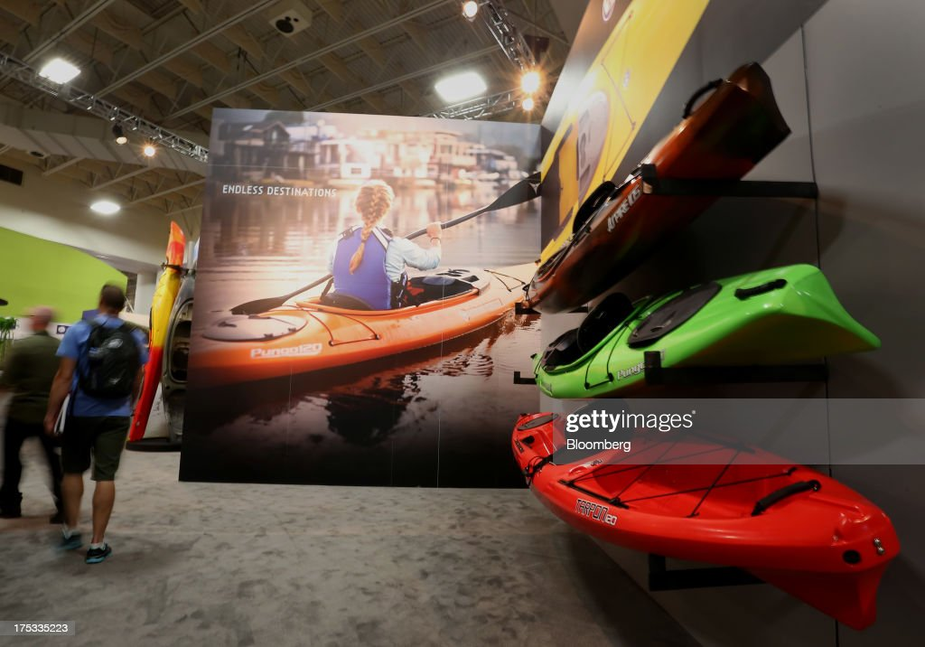 Attendees pass by kayaks displayed during the Outdoor Retailer Summer Market show in Salt Lake City, Utah, U.S., on Thursday, Aug. 1, 2013. Consumer spending in the U.S. rose in line with forecasts in June as Americans' incomes grew, a sign the biggest part of the economy is withstanding fiscal headwinds. Photographer: George Frey/Bloomberg via Getty Images