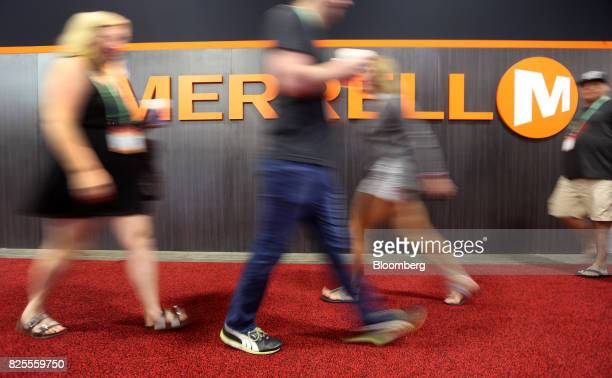 Attendees pass in front of Wolverine World Wide Inc Merrell brand signage displayed during the Outdoor Retailer Summer Market Show in Salt Lake City...