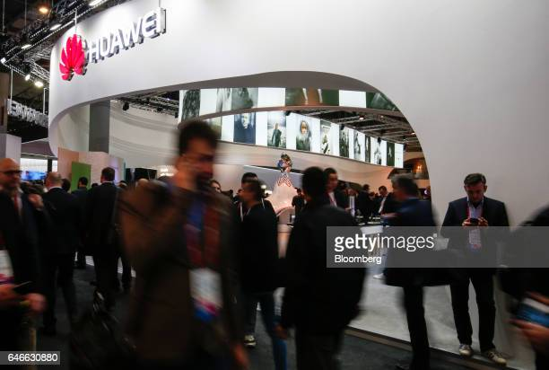 Attendees pass the Huawei Technologies Co Ltd stand on the third day of Mobile World Congress in Barcelona Spain on Wednesday March 1 2017 A theme...