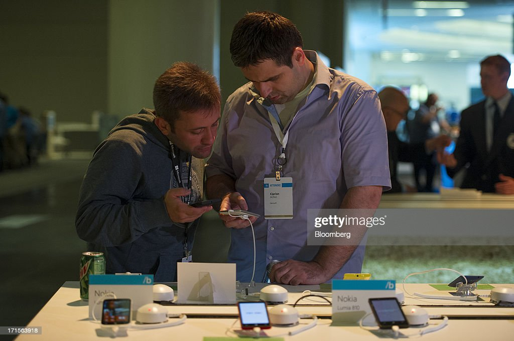 Attendees Petru Jucovschi, left, and Ciprian Jichici look at Nokia OYJ smart phones during the Microsoft Corp. Build Developers Conference in San Francisco, California, U.S., on Wednesday, June 26, 2013. Facebook Inc. is building an application for Microsoft Corp.'s Windows 8, adding one of the most popular programs still missing from the operating system designed to help Microsoft gain tablet customers. Photographer: David Paul Morris/Bloomberg via Getty Images