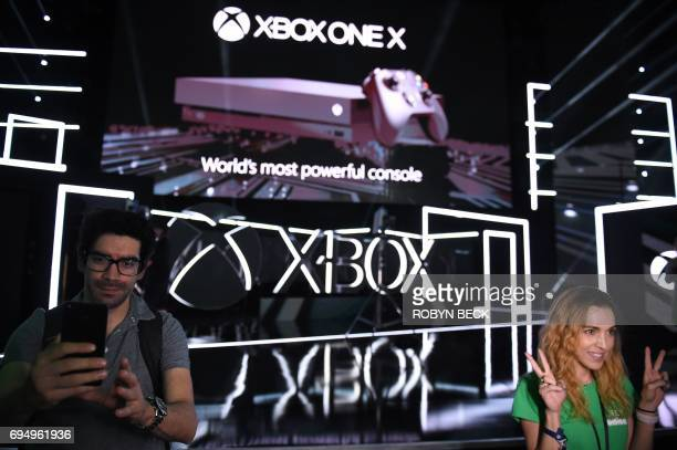 Attendees photograph themselves after the new Xbox One X was introduced at the Microsoft Xbox E3 2017 Briefing June 11 2017 at the Galen Center in...