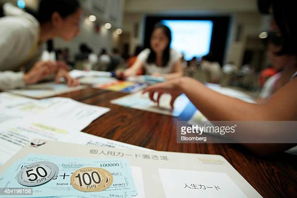 Attendees play a board game about finance and investing during a parentandchild investment class hosted by Japan Exchange Group Inc at the Tokyo...
