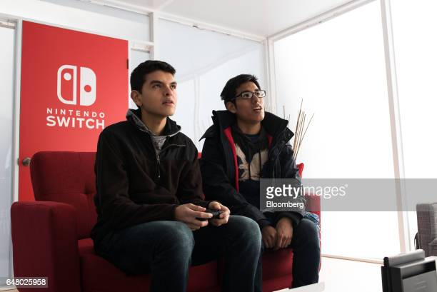 Attendees play a Nintendo Co Switch game console during the company's launch event in New York US on Friday March 3 2017 Nintendo shares rose on...