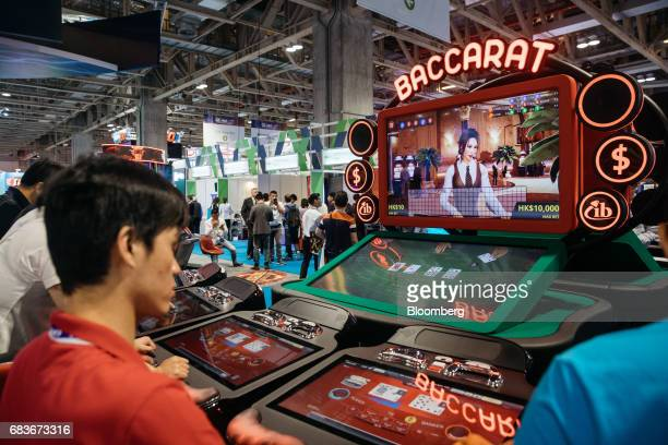Attendees play baccarat at a gaming machine at the Global Gaming Expo inside the Venetian Macau resort and casino operated by Sands China Ltd a unit...