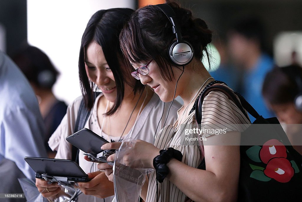 Attendees play games on Nintendo Co.'s 3DS LL handheld game consoles at the Level-5 Inc. booth during the Tokyo Game Show 2012 at Makuhari Messe on September 20, 2012 in Chiba, Japan. The annual video game expo, which is held from September 20 to 23, attracts thousands of business visitors and the general public with exhibitions of the upcoming game software and latest hardware.