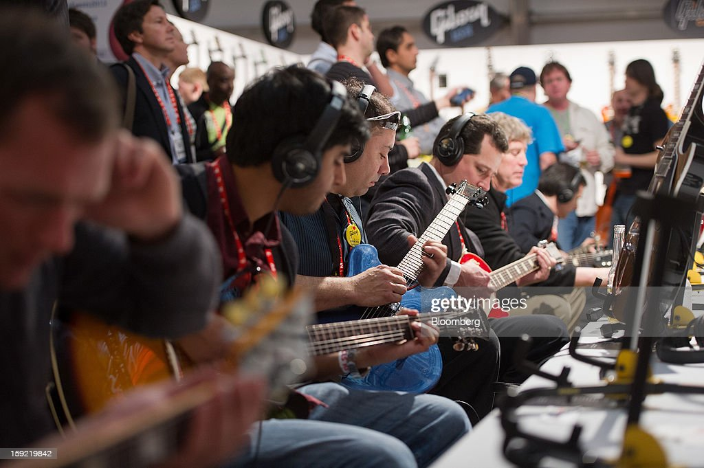 Attendees play Gibson Corp. guitars inside the Gibson tent at the 2013 Consumer Electronics Show in Las Vegas, Nevada, U.S., on Wednesday, Jan. 9, 2013. The 2013 CES trade show, which runs until Jan. 11, is the world's largest annual innovation event that offers an array of entrepreneur focused exhibits, events and conference sessions for technology entrepreneurs. Photographer: David Paul Morris/Bloomberg via Getty Images