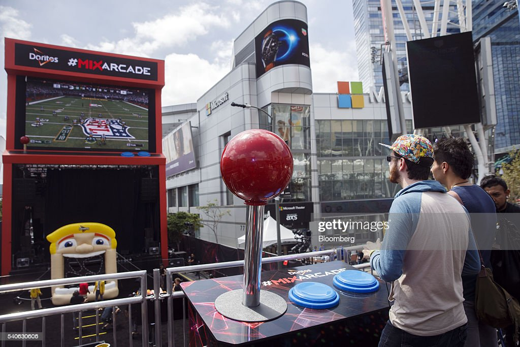 Attendees play the Electronic Arts Inc Sports 'Madden NFL 2017' video game on a giant screen at the Doritos #MixArcade fan experience during the E3...
