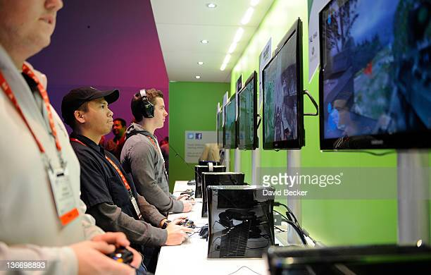 Attendees play video games at Microsoft's Xbox 360 display at the 2012 International Consumer Electronics Show at the Las Vegas Convention Center...