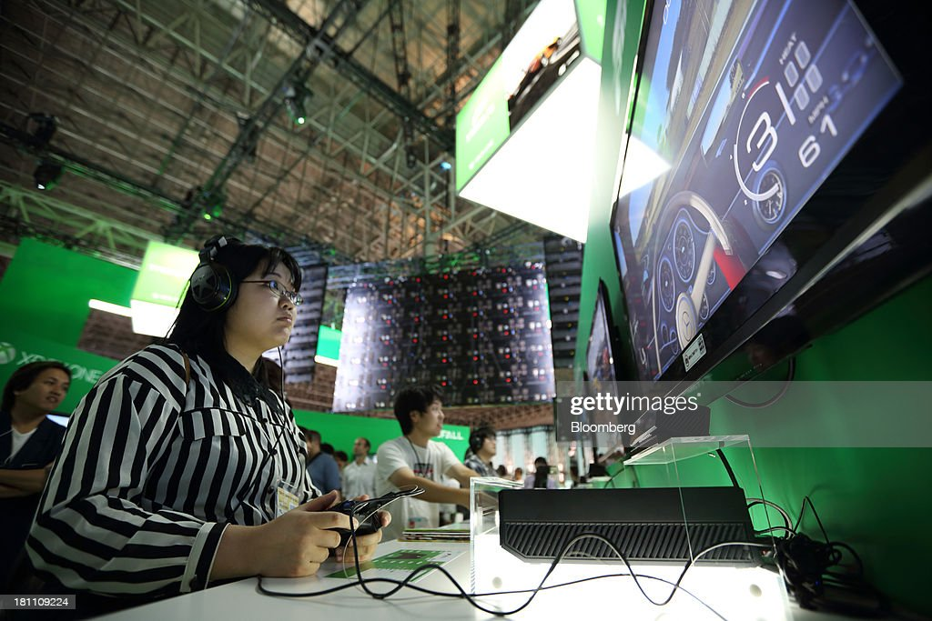 Attendees play video games on Microsoft Corp. Xbox One video game consoles at the Tokyo Game Show 2013 in Chiba, Japan, on Thursday, Sept. 19, 2013. Microsoft, the top U.S. seller of consoles for more than two years, plans to release the Xbox One in the U.S. on Nov. 22 while it will go on sale in Japan in 2014. Photographer: Tomohiro Ohsumi/Bloomberg via Getty Images