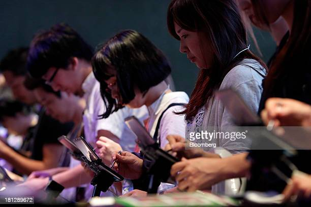 Attendees play video games on Nintendo Co 3DS handheld game players in the GungHo Online Entertainment Inc booth at the Tokyo Game Show 2013 in Chiba...