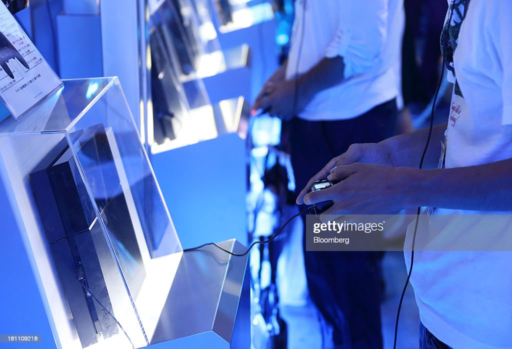 Attendees play video games on Sony Computer Entertainment Inc. PlayStation 4 (PS4) video game consoles at the Tokyo Game Show 2013 in Chiba, Japan, on Thursday, Sept. 19, 2013. Sony Corp. expects sales of its new PlayStation 4 console to reach 5 million units this financial year, with at least 20 games to be available as it competes with a new machine from Microsoft Corp. Photographer: Tomohiro Ohsumi/Bloomberg via Getty Images