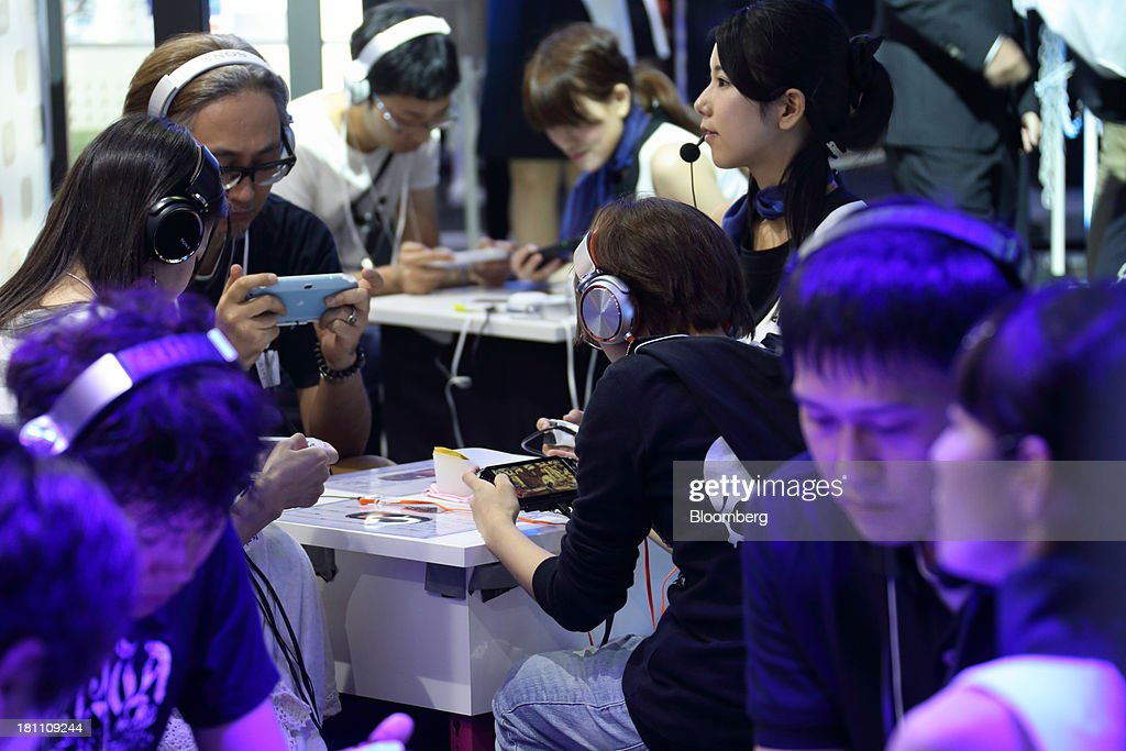 Attendees play video games on Sony Computer Entertainment Inc. PlayStation Vita (PS Vita) portable video game players at the Tokyo Game Show 2013 in Chiba, Japan, on Thursday, Sept. 19, 2013. The Tokyo Game Show runs till Sept. 22. Photographer: Tomohiro Ohsumi/Bloomberg via Getty Images