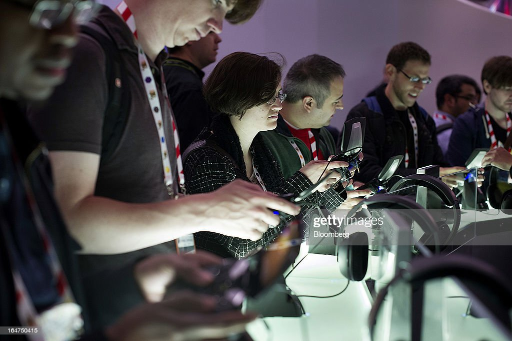 Attendees play with the new Nvidia Corp. Shield gaming device at the Game Developers Conference 2013 in San Francisco, California, U.S., on Wednesday, March 27, 2013. With over 22,500 attendees, the Game Developers Conference is the world's largest and longest-running professionals-only game industry event. Photographer: David Paul Morris/Bloomberg via Getty Images