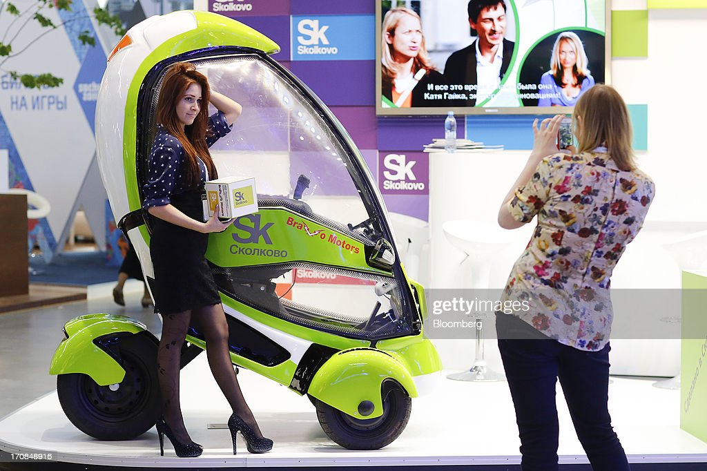 Attendees pose for photographs at the Skolkovo Foundation's 'tech city' pavilion display ahead of the St. Petersburg International Economic Forum 2013 (SPIEF) in St. Petersburg, Russia, on Wednesday, June 19, 2013. The Russian Deputy Prime Minister Igor Shuvalov told the conference that the country's World Trade Organization accession negotiations could be further delayed unless several remaining disputed matters are solved. Photographer: Simon Dawson/Bloomberg via Getty Images