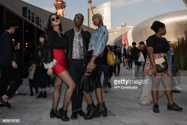 Attendees pose for photos between shows during Seoul fashion week at Dongdaemun Design Plaza in Seoul on October 20 2017 For Seoul's flamboyant...