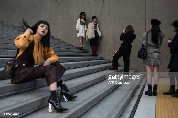 Attendees pose for photos during Seoul fashion week at Dongdaemun Design Plaza in Seoul on October 20 2017 For Seoul's flamboyant followers of...