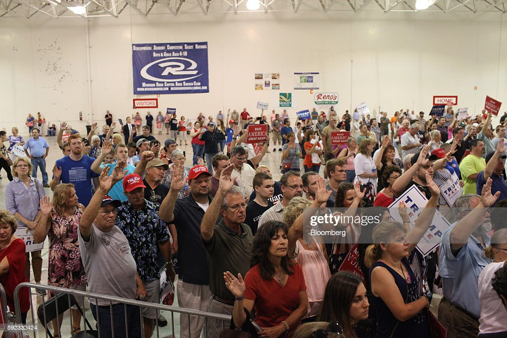 Attendees raise their hands while attending a campaign event for Donald Trump 2016 Republican presidential nominee not pictured in Lansing Michigan...
