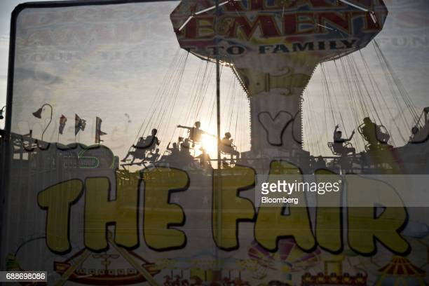 Attendees ride the Tornado swing during the Dreamland Amusements carnival in the parking lot of the Neshaminy Mall in Bensalem Pennsylvania US on...