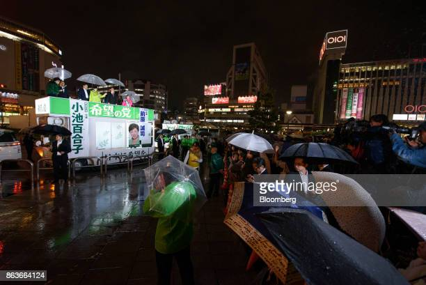 Attendees shelter under umbrellas as Yuriko Koike governor of Tokyo and leader of the Party of Hope top center speaks from a campaign van during an...