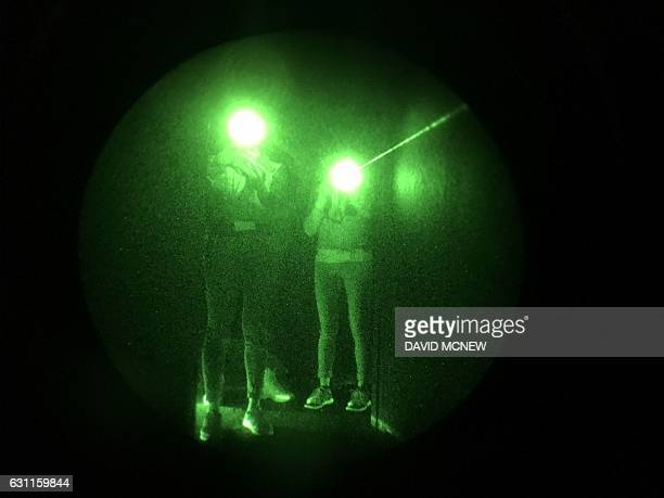 Attendees shoot at targets in the dark using military night vision technology at the History exhibit to promote the new television series 'Six' based...
