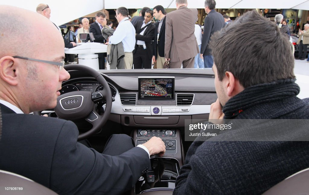 CES attendees sit in a display of the Audi interior at the Audi booth during the 2011 International Consumer Electronics Show at the Las Vegas Convention Center January 7, 2011 in Las Vegas, Nevada. CES, the world's largest annual consumer technology tradeshow, runs from January 6-9 and is expected to feature 2,700 exhibitors showing off their latest products and services to about 126,000 attendees.