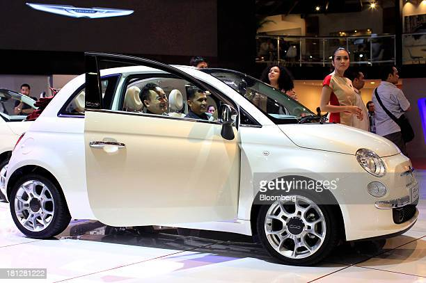 Attendees sit in a Fiat SpA Fiat 500 vehicle at the 21st Indonesia International Motor Show in Jakarta Indonesia on Thursday Sept 19 2013 The Motor...