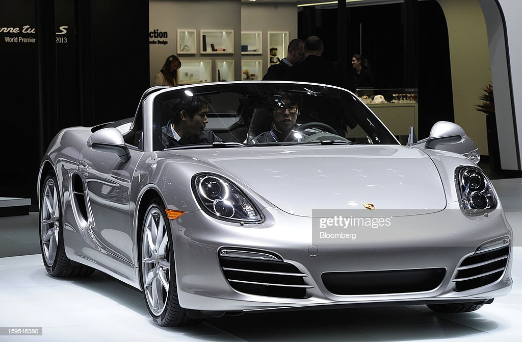 Attendees sit in a Porsche AG vehicle during the 2013 North American International Auto Show (NAIAS) in Detroit, Michigan, U.S., on Tuesday, Jan. 15, 2013. The Detroit auto show runs through Jan. 27 and will display over 500 vehicles, representing the most innovative designs in the world. Photographer: David Paul Morris/Bloomberg via Getty Images