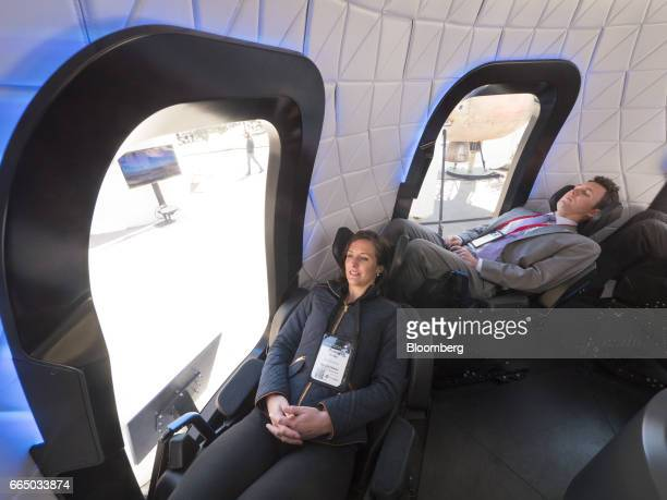 Attendees sit inside the high fidelity crew capsule mock up of the Blue Origin LLC New Shepard system during the Space Symposium in Colorado Springs...