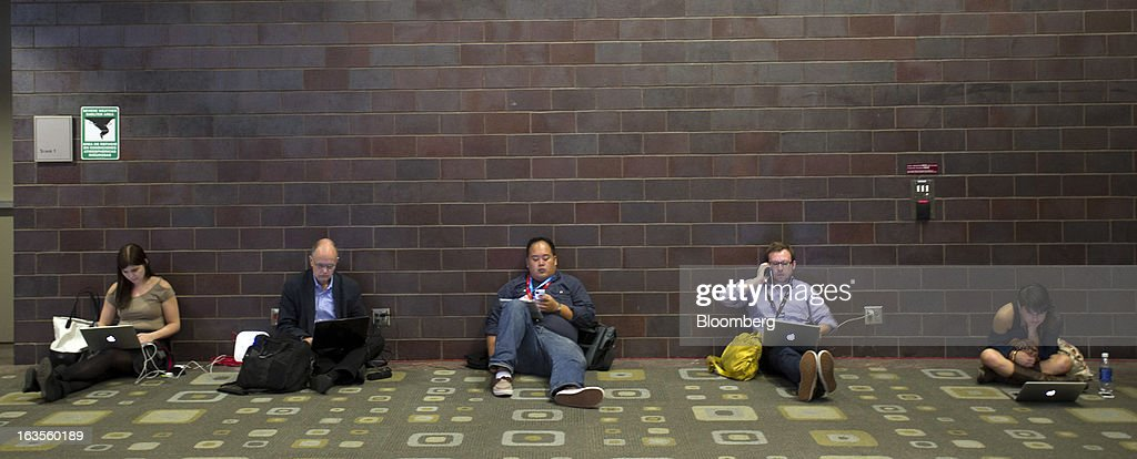 Attendees sit on the floor as they work on their laptops and smart phones at the South By Southwest Conference (SXSW) in Austin, Texas, U.S., on Monday, March 11, 2013. The 20th annual SXSW Interactive Festival takes place from March 8-12. Photographer: David Paul Morris/Bloomberg via Getty Images