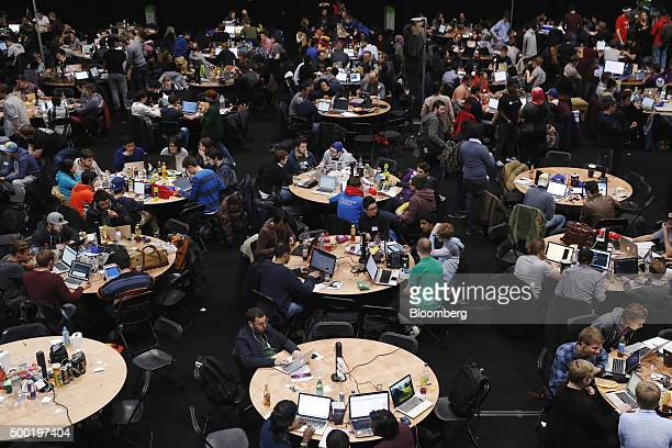 Attendees sitting at round tables and working on laptop computers participate in the TechCrunch Disrupt London 2015 Hackathon in London UK on...