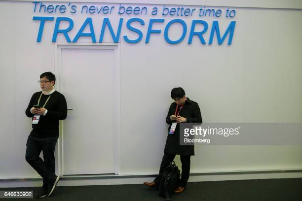 Attendees stand below a slogan reading 'There's never been a better time to transform' on the third day of Mobile World Congress in Barcelona Spain...