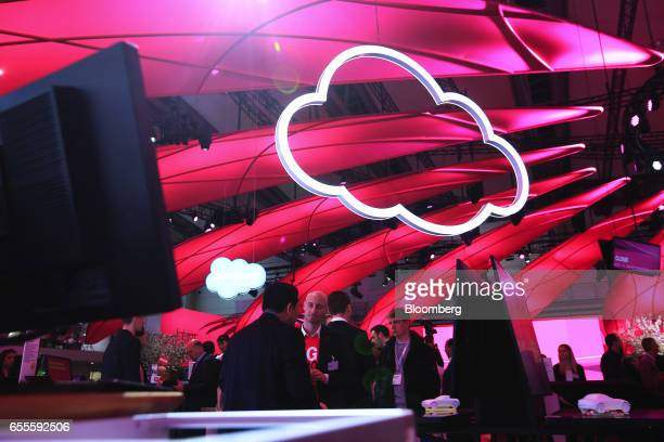 Attendees stand beneath icloud symbols in the Deutsche Telekom pavilion at the CeBIT 2017 tech fair in Hannover Germany on Monday March 20 2017...
