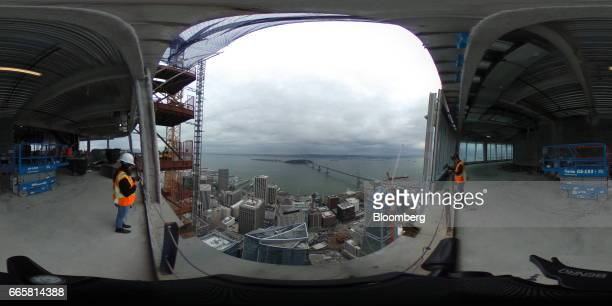 Attendees stand during a tour as the Bay Bridge is seen at a topping off ceremony for the Salesforce Tower in San Francisco California US on Thursday...