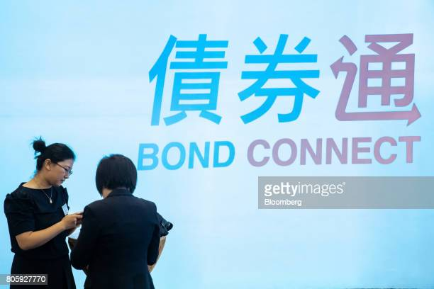 Attendees stand in front of signage for the ChinaHong Kong Bond Connect at the Hong Kong Stock Exchange in Hong Kong China on Monday July 3 2017 The...