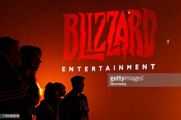 Attendees stand in front of the logo for Blizzard Entertainment Inc a unit of Activision Blizzard Inc as they watch a trailer for the company's...