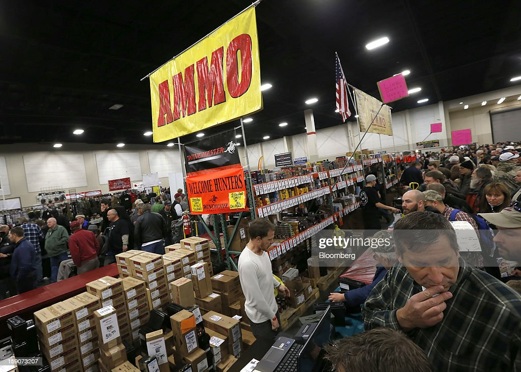 Attendees stand in line in a section that sells ammunition at the Rocky Mountain Gun Show in Sandy, Utah, U.S., on Saturday, Jan. 5, 2013. A working group led by Vice President Joe Biden is seriously considering measures that would require universal background checks for firearm buyers, track the movement and sale of weapons through a national database, strengthen mental health checks and stiffen penalties for carrying guns near schools or giving them to minors. Photographer: George Frey/Bloomberg via Getty Images