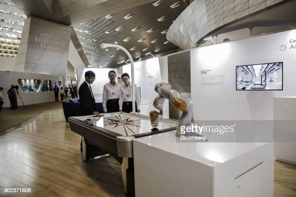 Attendees stand opposite a Kuka LBR iiwa robotic arm at an air hockey table at the World Economic Forum Annual Meeting of the New Champions in Dalian...