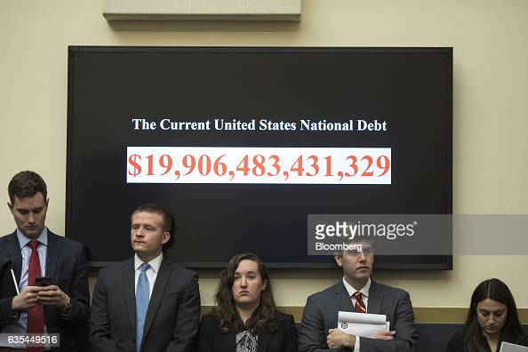 Attendees stand under a monitor displaying the current US national dept figures during a House Financial Services Committee hearing with Janet Yellen...