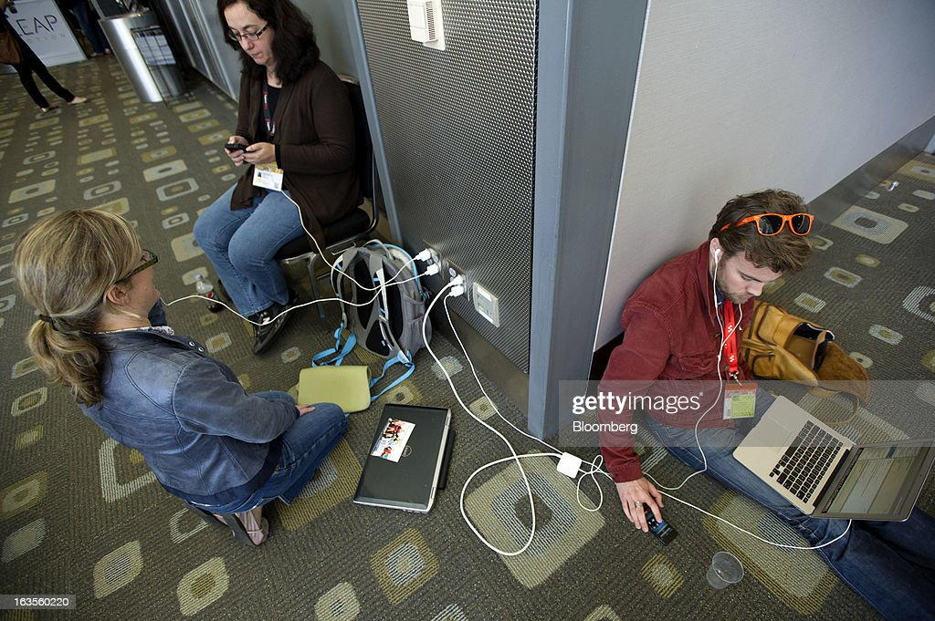 Attendees take advantage of electrical outlets to charge their devices at the South By Southwest Conference (SXSW) in Austin, Texas, U.S., on Monday, March 11, 2013. The 20th annual SXSW Interactive Festival takes place from March 8-12. Photographer: David Paul Morris/Bloomberg via Getty Images