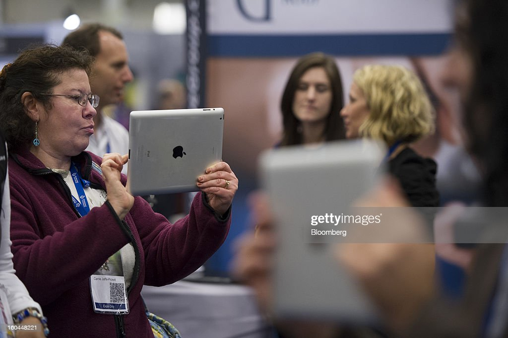 Attendees take photographs and record videos using Apple Inc. iPads at the Macworld/iWorld conference at the Moscone Center West in San Francisco, California, U.S., on Thursday, Jan. 31, 2013. This year's conference, titled 'The Ultimate iFANEvent,' brings together attendees to celebrate Apple Inc. technology and learn more about products and services for Apple users. Photographer: David Paul Morris/Bloomberg via Getty Images