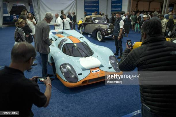 Attendees take photographs of a 1970 Porsche AG 917k race vehicle formerly driven by actor Steve McQueen in the movie 'Le Mans' at the Gooding and...