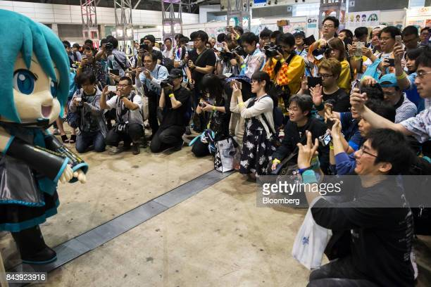 Attendees take photographs of a performer wearing a mascot costume of Hatsune Miku a virtual pop star and the voice behind Crypton Future Media Inc's...