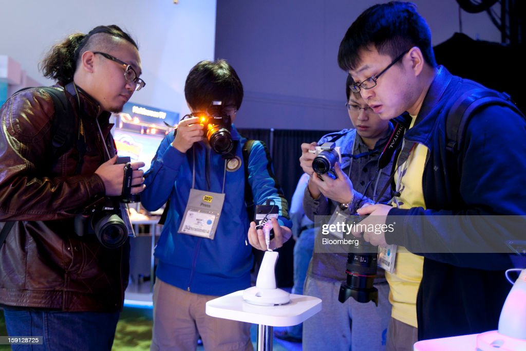 Attendees take photographs of a reference design smartphone intended for emerging markets at the Intel Corp. booth during the 2013 Consumer Electronics Show in Las Vegas, Nevada, U.S., on Tuesday, Jan. 8, 2013. The 2013 CES trade show, which runs until Jan. 11, is the world's largest annual innovation event that offers an array of entrepreneur focused exhibits, events and conference sessions for technology entrepreneurs. Photographer: Andrew Harrer/Bloomberg via Getty Images