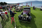 Attendees take photographs of automobiles on display during the 2014 Pebble Beach Concours d'Elegance in Pebble Beach California US on Sunday Aug 17...